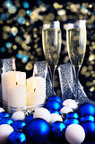 Burning candles, Christmas ornaments and champagne glasses Royalty Free Stock Photos