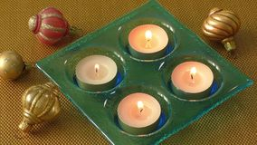 Burning candles in a Christmas setting with seasonal decorations. Burning candle in a Christmas setting with seasonal decorations stock video footage