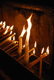 Burning candles in a church. Candles in a church burning during a religious ceremony Stock Photos