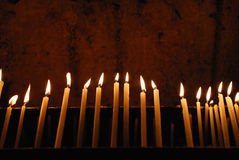 Burning candles in a church. Candles burning in a Church during a religious ceremony Royalty Free Stock Image