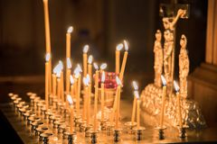 Burning candles in the church against the background of icons Stock Photos