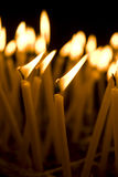 Burning candles in a church on a dark background Stock Photo