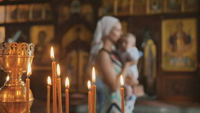 Burning candles in church, mother with baby on blurred background stock footage