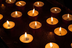 Burning Candles. Closeup photo of candles burning inside a church Royalty Free Stock Image