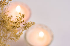 Burning candles in crystal cups on white background, delicate small beige spring flowers, top view, defocused Stock Photography