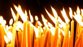 Burning candles on dark background. Burning candles. Celebration event or religious memorial attribute of warmth and sincerity royalty free stock image
