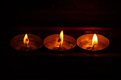 Burning candles on dark background with warm light Stock Photo