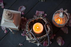 Burning candles in a decorative basket and lantern. Royalty Free Stock Image