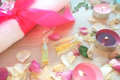 Burning candles with essential spa oil, rose flower petals and white towel on wooden table background royalty free stock photo