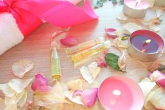 Burning candles with essential spa oil, rose flower petals and white towel on wooden table background royalty free stock photos