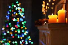Burning candles on fireplace and Christmas tree. With fairy lights at night. Stylish room interior royalty free stock photos