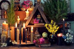 Burning candles, flowers and crystal gem stones on witch table. Wicca, esoteric, divination and occult concept with vintage magic objects for mystic rituals stock photo