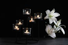 Burning candles and flowers on dark background. Funeral symbol royalty free stock image