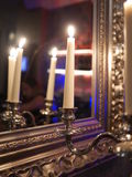 Burning candles in front mirror Royalty Free Stock Photos