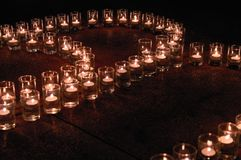 Burning candles in glass flasks stand on the dark floor of celebraiotn hall. Royalty Free Stock Photos