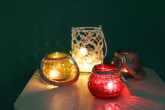 Burning candles in glass holders. On table Stock Images