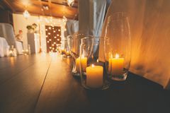Burning candles in glass vases on the wooden floor close-up. Festive wedding interior, beautifully decorated romantic place full royalty free stock photography