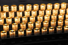 Burning candles in glasses on the altar in the cathedral Stock Photos