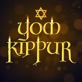 Burning candles in glossy golden Yom Kippur text with star of da. Vid on brown bokeh background Royalty Free Stock Photo