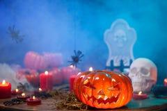 Burning candles at halloween celebration wtih creepy pumpkin near. Mysterious mist stock image