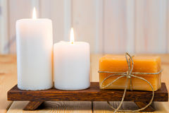 Burning candles and handmade soap on wooden support Stock Image