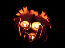 Burning candles and hands in darkness Stock Image