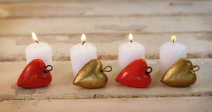 Burning candles with heart shape pendant on wooden plank stock footage