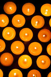 Burning candles. Lots of yellow light candles close-up on black background Royalty Free Stock Photo