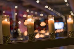 Burning candles at night. With blurred background of a Christmas party Royalty Free Stock Images