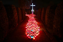 Burning candles at night. A night view of hundreds of candles lit for the deceased family members and friends in front of the cross at city cemetery on All Stock Photography