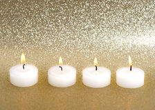 Burning candles over golden background Stock Image