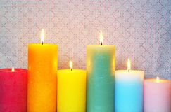Burning Candles In Pastel Colors. Six burning rustic candles in pastel colors on vintage background with pink pattern stock image