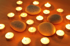 Burning candles and pebbles for aromatherapy Stock Photos