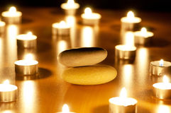 Burning candles and pebbles for aromatherapy Stock Photo