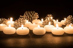 Burning candles with pine apples at a black background Stock Photography