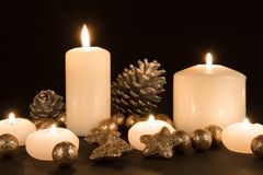 Burning candles with pine apples and gilded stars on a black background Royalty Free Stock Photo