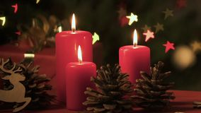 Burning candles, pinecones and Christmas star lights creating festive atmosphere. Stock footage stock video footage