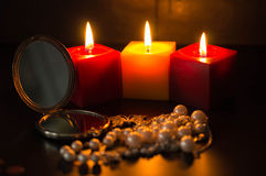 Burning candles, pocket mirror and beads Stock Images