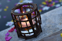 Burning candles by pool. Burning candles in burner by pool with scattered colorful petals on water Stock Photos