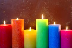 Burning Candles In Rainbow Colors. Six burning candles in rainbow colors on old grungy background stock photo