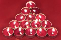 Burning candles on red. Candles arranged in tree shape on red background Stock Photo