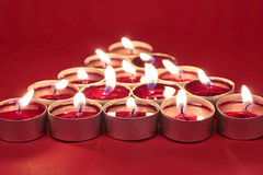 Burning candles on red. Candles arranged in tree shape on red background Stock Images