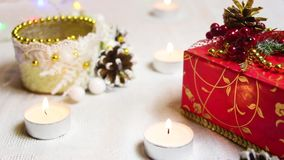 Burning candles, a red gift box and decorative ornaments with shimmering flashlights stock footage