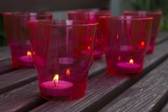 Burning candles in red plastic glasses on vintage wooden background. Selective focus stock image