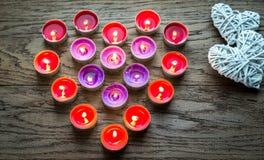 Burning candles with retro cane hearts Stock Photo