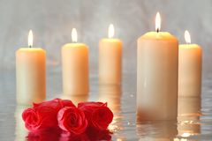 Burning candles with roses Stock Photography