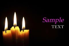 Burning candles with sample text. In black background Stock Images