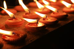 Burning candles in sconces on black background Stock Image