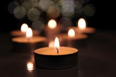 Many candle flames glowing on dark background. Close-up. Free space. royalty free stock photo