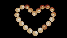 Burning candles shape heart. Burning candles in the shape of a heart on a black background stock video footage